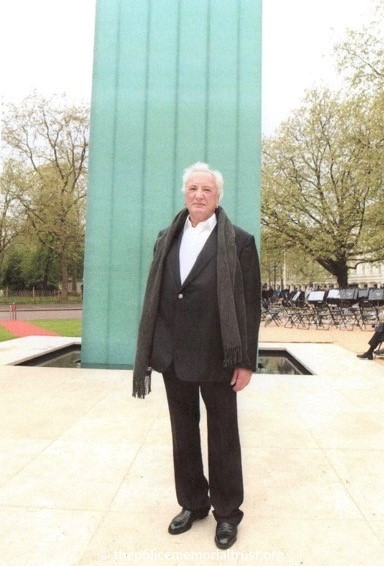 Mr. Michael Winner stands at the blue glass column and reflecting pool of the newly opened National Police Memoria