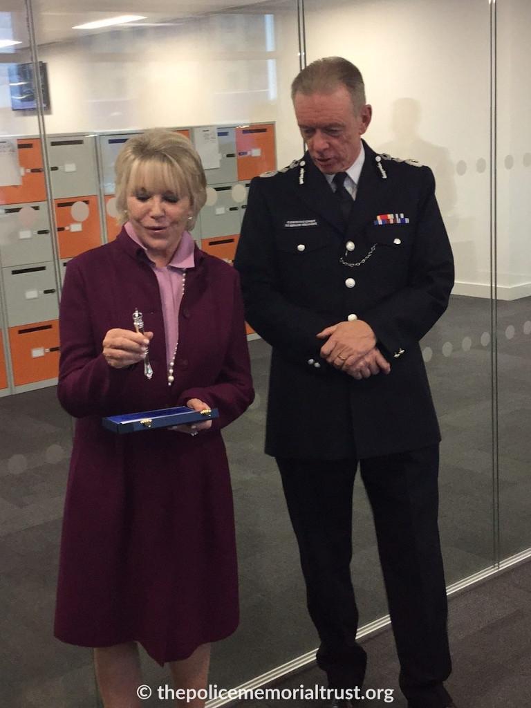 The Commissioner Sir Bernard Hogan Howe presenting a Baton of Honour to Geraldine Winner