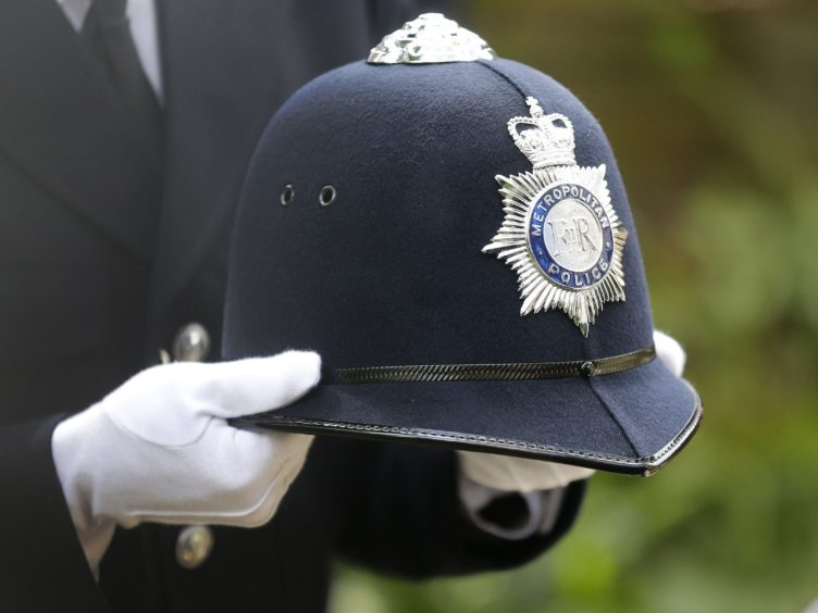 police officer with white gloves holding a helmet