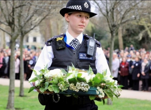 Female police officer carrying flower wreath